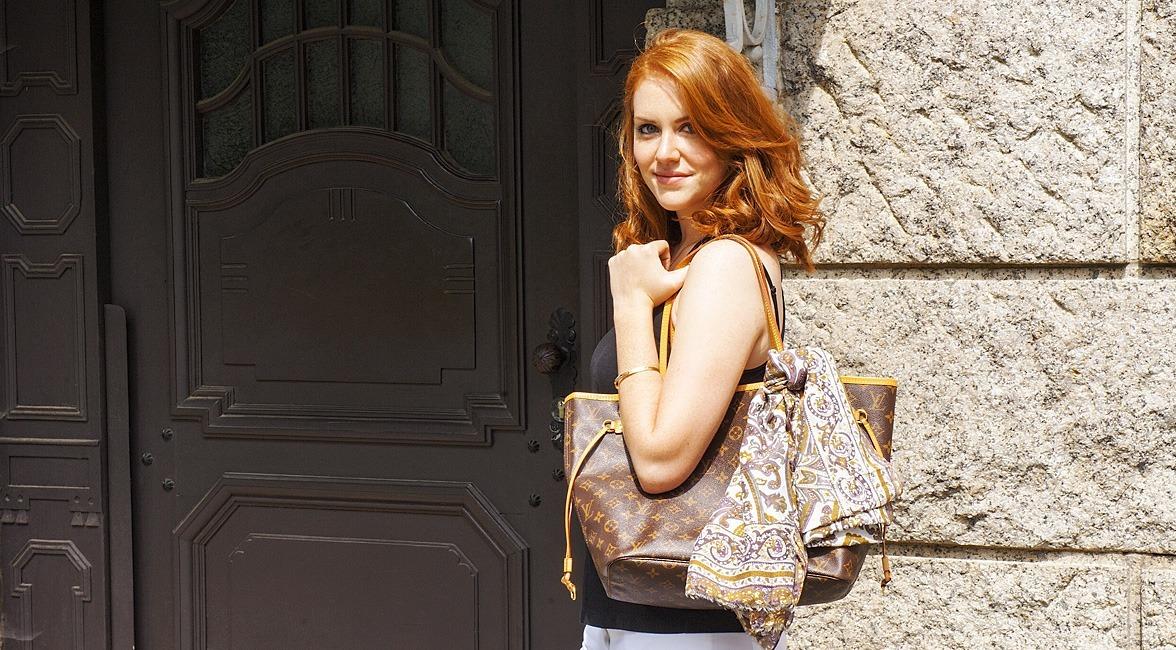 Eine Frau trägt eine Handtasche mit einem farblich dazu passenden Sommerschal als Accessoire