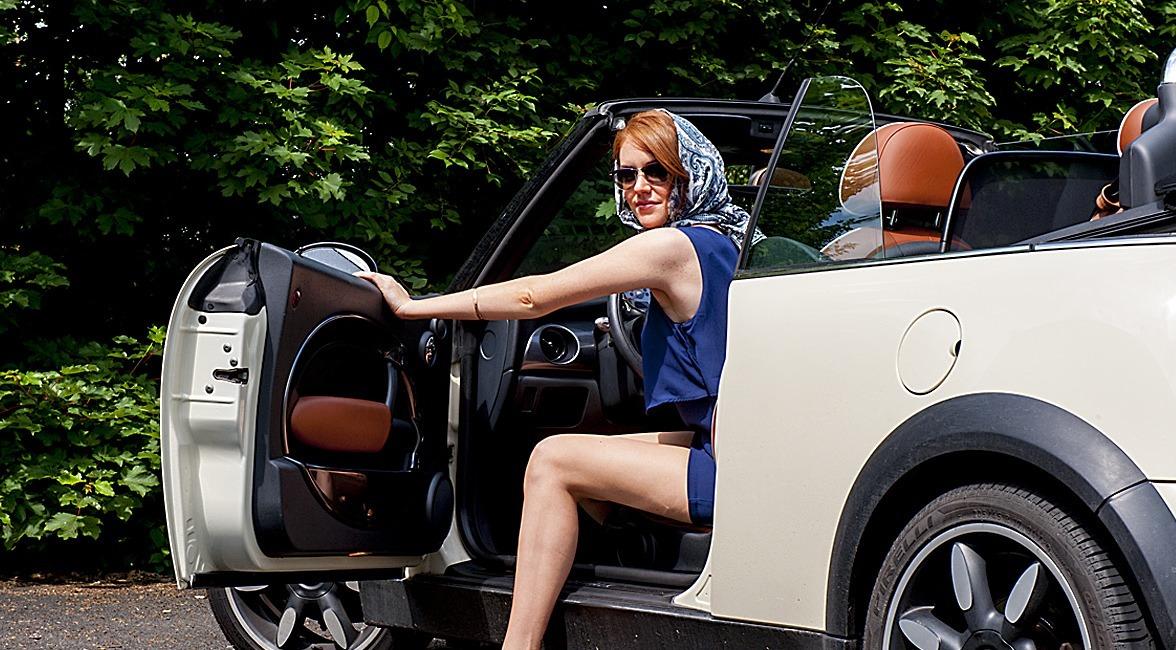 Eine Frau mit stylishem Kopftuch steigt á la Jacky Kennedy aus einem Cabrio