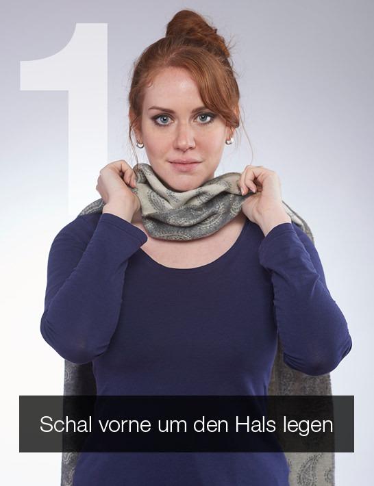 Ein Schal wird von vorne nach hinten mittig um den Hals gelegt.