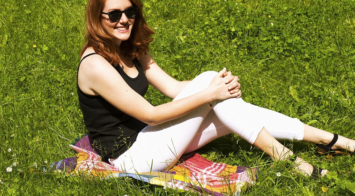 Eine Frau schützt ihre helle Hose indem sie auf einem Sommerschal in der Wiese sitzt