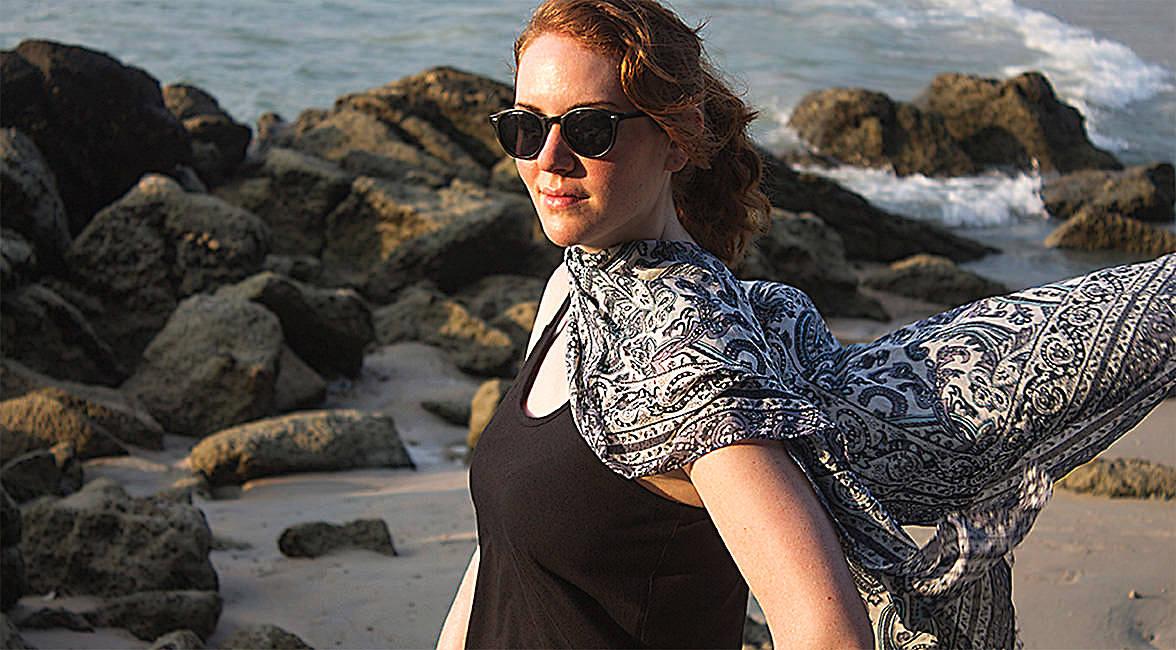Eine Frau steht mit wehendem Schal um den Hals am Strand